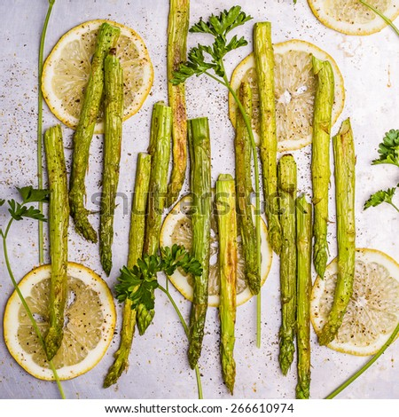 Grilled asparagus with lemon and parsley on a baking sheet. - stock photo