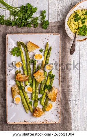 Grilled asparagus with quail eggs on a white wooden background - stock photo