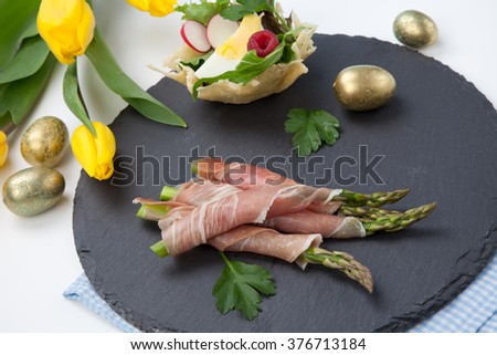 Grilled asparagus wrapped in prosciutto and parmesan baskets filled with fresh garden salad. Easter decorated eggs, tulips flowers, holiday theme.