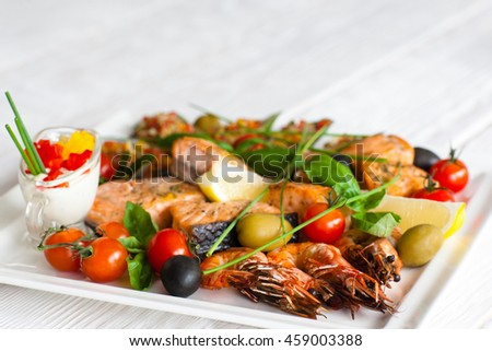 Grilled assorted seafood with sauce, blurred background with copyspace for text, focus on roasted shrimps with tomatoes and olives - stock photo
