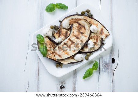 Grilled aubergine slices with capers, mozzarella and basil - stock photo