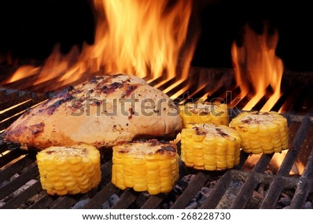 Grilled BBQ Chicken Breast and Corn Rings Close-Up. Hot Flaming Grill In The Background. - stock photo