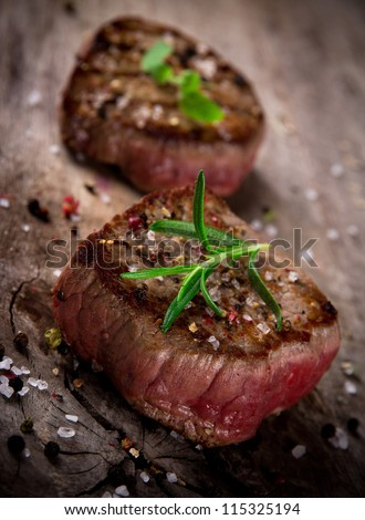 Grilled bbq steaks on wooden background - stock photo