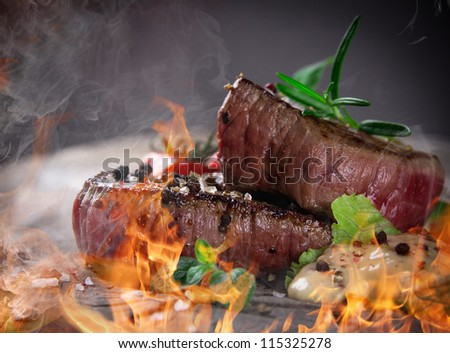 Grilled bbq steaks with fire flames - stock photo