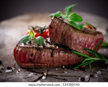 Grilled bbq steaks with fresh herbs and tomatoes - stock photo