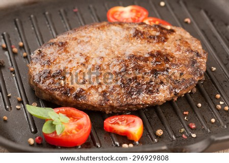 Grilled beef burger with cherry tomatoes