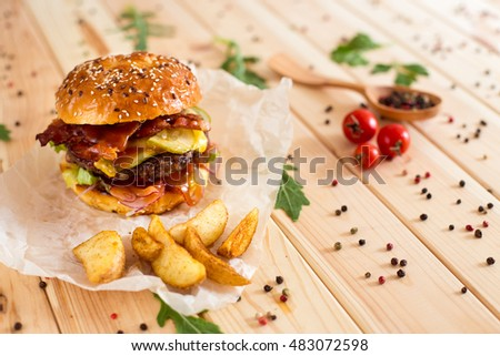 grilled beef burger with lettuce and mayonnaise on a rustic wooden table