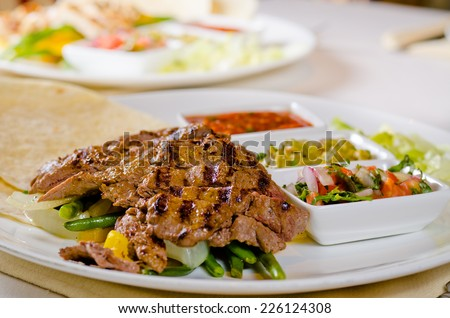 Grilled beef fajitas on green beans with Mexican sauces, hot tomato and chili salsa and corn tortillias - stock photo