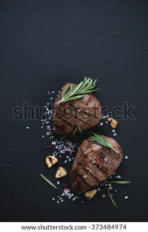 Grilled beef filet mignon steaks, black wooden surface, top view