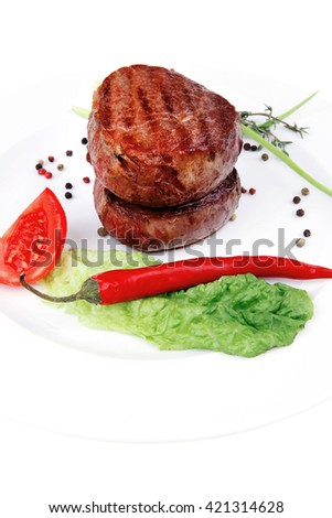 grilled beef fillet medallions on noodles with red hot chili pepper and salad leaf on white plate isolated over white background - stock photo