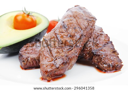 grilled beef fillet with avocado and tomatoes on white plate isolated over white background - stock photo
