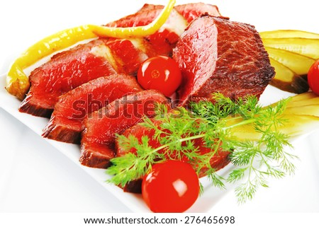 grilled beef meat entrecote on white plates with peppers and tomato isolated on white background - stock photo