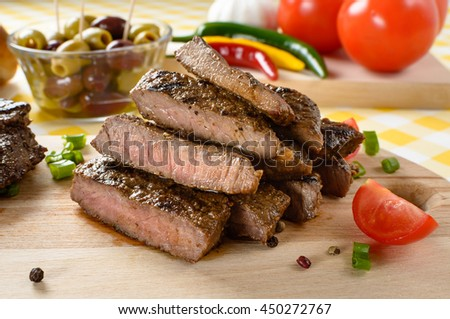 Grilled beef meat on wooden plate with vegetables and olives in the background.