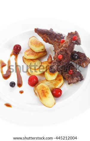 grilled beef meat with berries fried potatoes and cherry under sweet honey sauce on white plate isolated over white background - stock photo