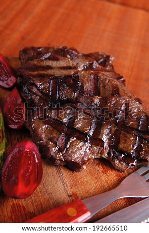 grilled beef pork meat steak fillet with asparagus  hot red peppers and cutlery on wooden cutting plate over wooden table