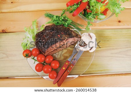 grilled beef sliced on transparent plate with salad bowl - stock photo
