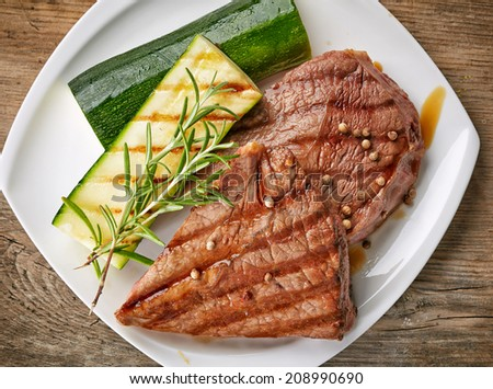 grilled beef steak and zucchini on white plate - stock photo