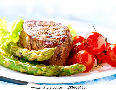 Grilled Beef Steak Meat with Vegetables - Asparagus, Cherry Tomato and Lettuce. Steak Dinner. Food - stock photo