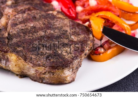 Grilled beef steak on a white plate on grey background. Closeup. Selective focus.