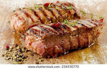 Grilled Beef steak on  a wooden cutting board . Selective focus