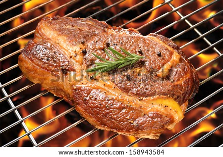 Grilled beef steak on the flaming grill - stock photo