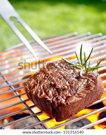 Grilled beef steak on the grilling pan outdoors - stock photo
