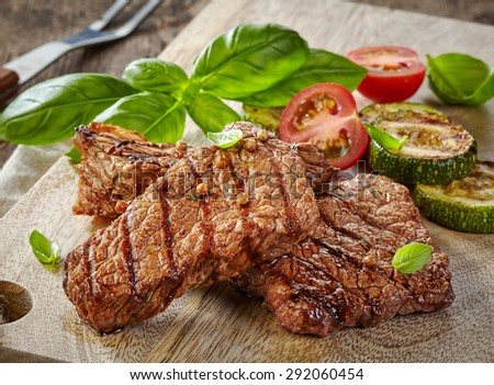 grilled beef steak portion served with roast zucchini and tomatoes on wooden cutting board - stock photo