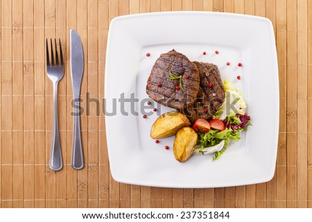 Grilled beef steak with baked potatoes and vegetables on plate - stock photo