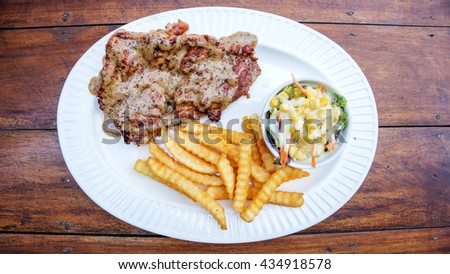 Grilled beef steak with french fries and corn salad. - stock photo
