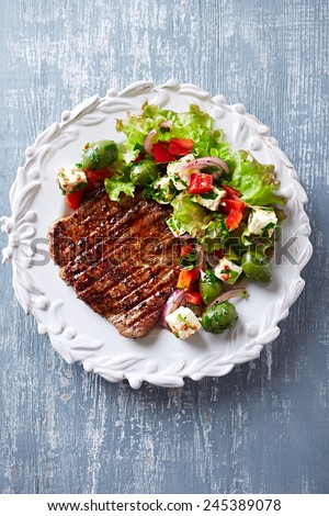Grilled beef steak with mediterranean-style salad - stock photo
