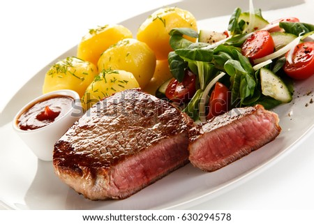 Grilled beef steak with potatoes and vegetable salad