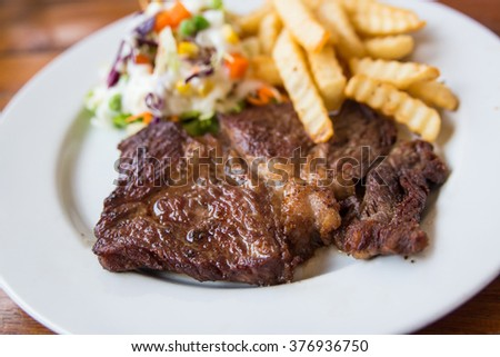 Grilled beef steak with salad and french fries.