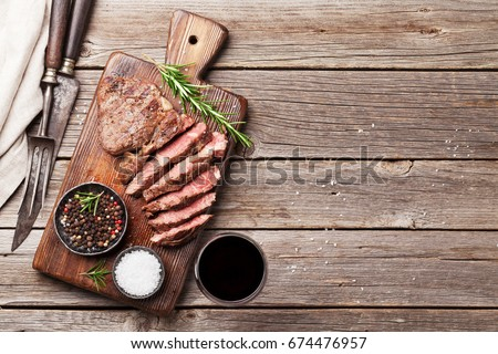 Grilled beef steak with spices on cutting board and red wine. Top view with copy space