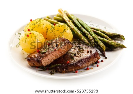Grilled beef steaks and asparagus on white background