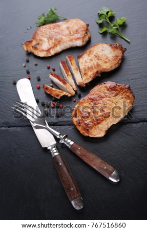 Grilled beef  steaks with fork and knife on slate stone. Closeup