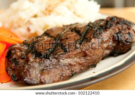 grilled beef tenderloin steak with mashed potatoes, steak drippings and sauteed carrots - stock photo