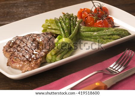Grilled beef tenderloin with asparagus and tomatoes