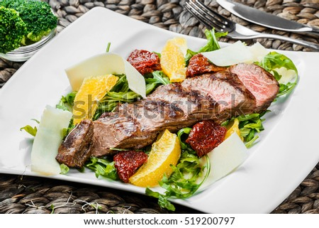 Grilled beef with orange fruit, arugula, parmesan cheese and sun-dried tomatoes on bamboo background. Traditional meat for Holidays. Top view