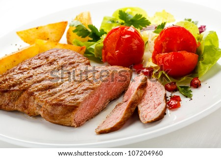 Grilled beefsteaks, baked potatoes and vegetable salad - stock photo