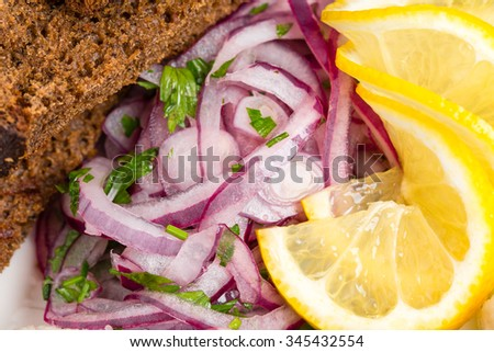 Grilled bread and marinated red onion as a garnish for herring fillet. Macro. Photo can be used as a whole background. - stock photo