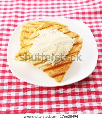 Grilled bread with butter on tablecloth - stock photo