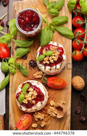Grilled brie cheese with cranberry jam and walnuts on old wooden background - stock photo