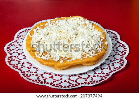 Grilled bun with mozzarella cheese on a red background - stock photo
