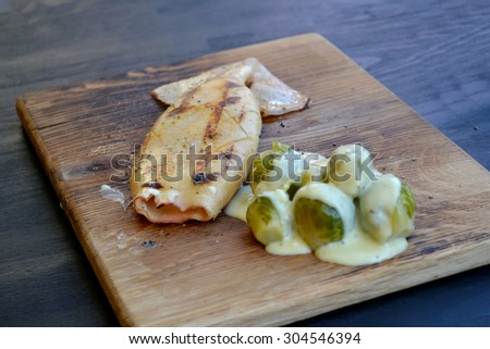 Grilled calamari with Brussels sprouts covered in sauce on wooden board - stock photo
