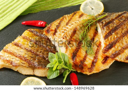 grilled carp with chili peppers, dill and lemon