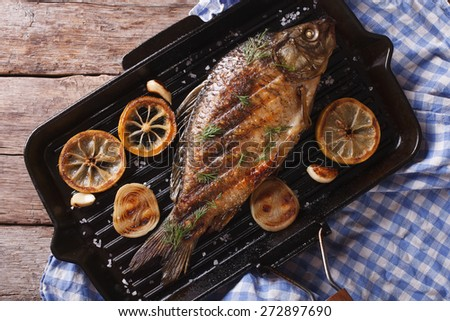 Grilled carp with lemon in a grill pan , horizontal view from above closeup  - stock photo