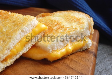 Grilled cheese sandwich  (made with thickly sliced french bread) on wooden cutting board.  Closeup with selective focus on front edge of sandwich. - stock photo