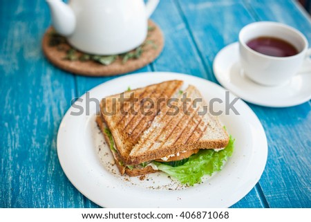 Grilled cheese sandwich on a white plate with cap of tea - stock photo