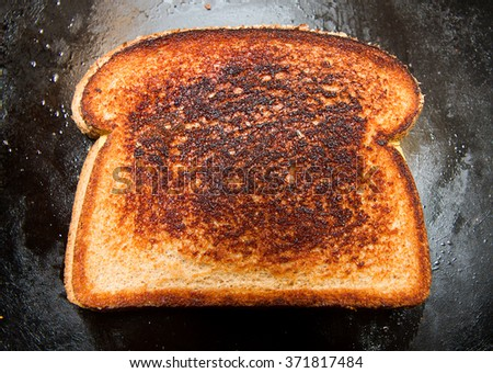 Grilled cheese sandwich that has a slightly burnt look to it - stock photo