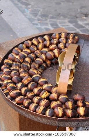 Grilled chestnuts for sale in a market stall - stock photo